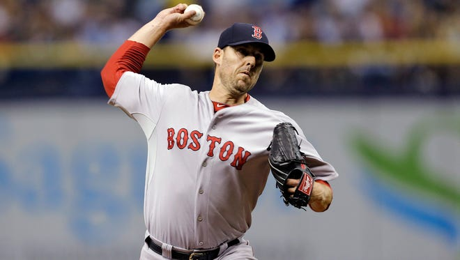 Boston Red Sox starting pitcher John Lackey delivers to the Tampa Bay Rays during the first inning of a baseball game Saturday, July 26, 2014, in St. Petersburg, Fla.