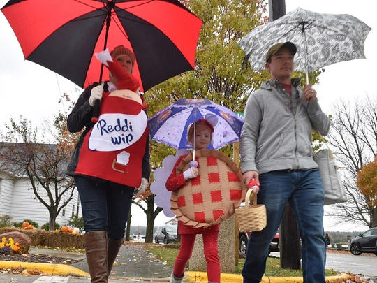 Faith Tislau is disguised as a cherry pie and her 3-month-old sister Grace is the can of whipped cream as the girls trick-or-treat with their parents, Bevin and Andy Tislau, in Fish Creek during last year's Jack O'Lantern Days.