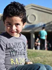 Five-year-old Christopher sits by the entrance of John Adams Elementary School on Thursday. Due to its low number of students, Desert Sands Unified School District has announced the school closure by the end of the year.