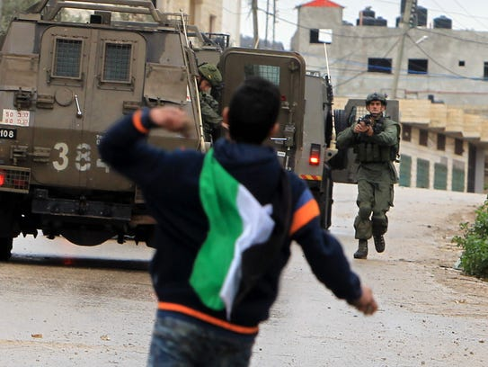 A Palestinian youth throws stones toward Israeli military