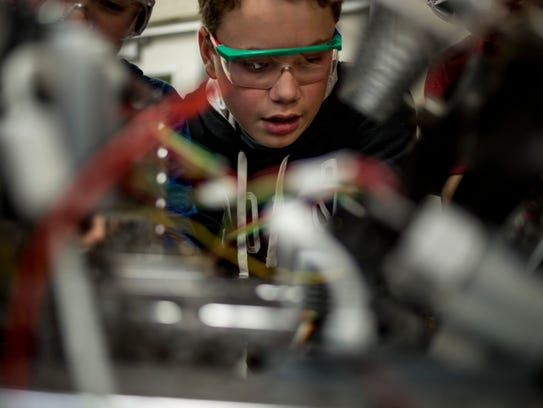 Connor Nesbitt, 14, looks closely at a component of