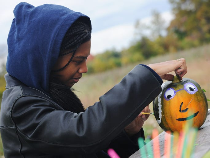 As the 296 acres of Palmer Park unfold behind her, Briana Thomas, 24, paints a friendly face on her pumpkin at Harvest Fest in Detroit on October 5, 2014. Hosted by the nonprofit People for Palmer Park,the annual event featured an afternoon of free hayrides, pony rides, arts and crafts, a petting zoo and tastes of fresh apples and grilled corn.