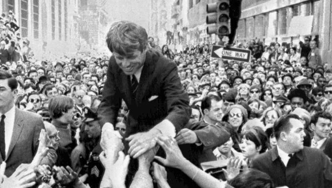 In this April 2, 1968 file photo U.S. Sen. Robert F. Kennedy, D-NY, shakes hands with people in a crowd while campaigning for the Democratic party's presidential nomination on a street corner, in Philadelphia.