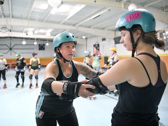 Dixie Kicks, Crystal Provenzano, helps Ella Conder with her elbow pads at the start of during Blue Ridge Rollergirls Derby School at Sk8t Depot in Hendersonville on Wednesday, Oct. 4, 2017. While it is a full-contact sport safety gear and rules about contact, such as no elbowing other skaters, make the sport as safe for skaters as possible.