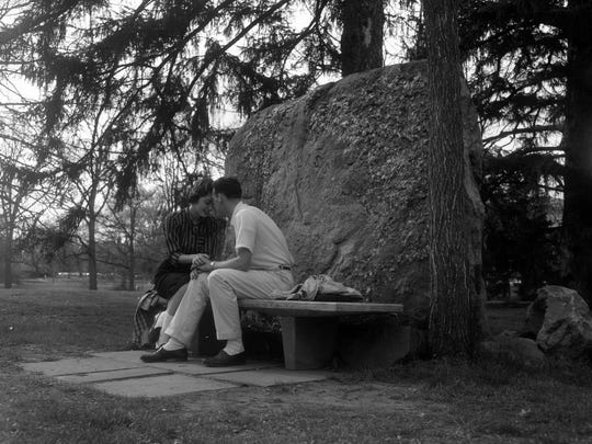 "A man and woman are sitting on the bench, in front of ""Engagement Rock,"" while holding each others hands and foreheads touching, April 21, 1958."