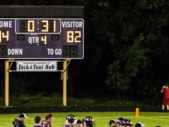 A fan takes a picture of the scoreboard as the record