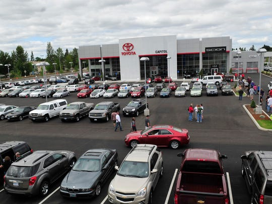 Drivers move cars onto the lot at the new Capitol Auto Group location off Salem Parkway Sunday, July 22, 2012.