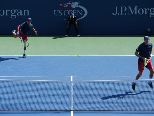 Mike Bryan hits a serve while Bob waits at the net