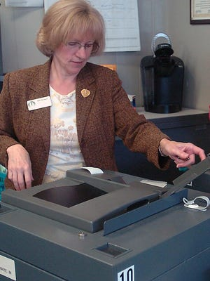 Highland Township Clerk Mary McDonell checks equipment before a recent election.