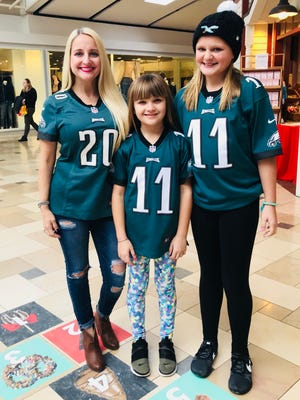 Gabby Hajduk and her daughters Chloe and Izzy from Deptford, N.J., wait in line to meet Eagles players Zach Ertz and Jake Elliot at a public event.