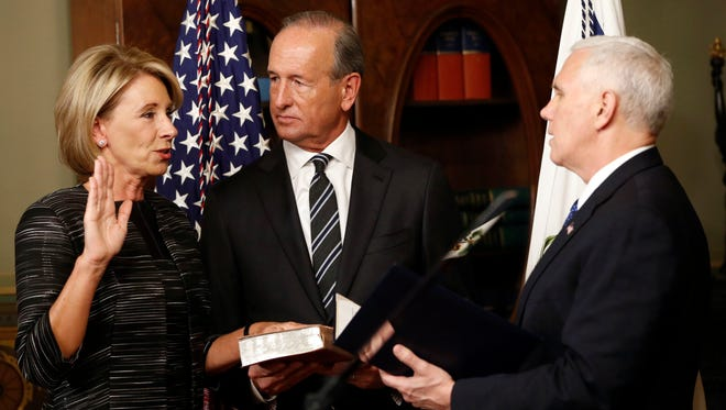 Vice President Mike Pence, right, swears in Education Secretary Betsy DeVos on Feb. 7, as DeVos' husband, Dick DeVos, watches.