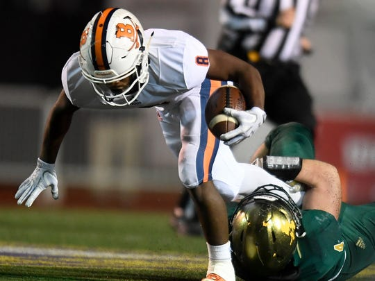 Knoxville Catholic's Jack Mahoney (4) takes down Beech's Kaemon Dunlap (8) during the first half of the Class 5A state championship game at Tucker Stadium in Cookeville, Tenn., Thursday, Nov. 30, 2017.