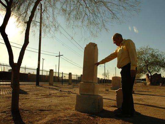 """Frank Barrios of the Pioneer Cemetery Association in downtown Phoenix visits the grave of Tom Graham, who was the last man killed in the """"Pleasant Valley War.""""  His death took place in Tempe at the corner of what is known today as the corner of Broadway and Priest."""