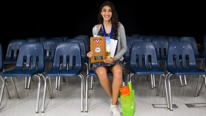 Surya Dodia, from North Naples Middle School, sits with her plaque after winning the final round of the Collier/Lee 2017 Spelling Bee at North Naples Middle School in North Naples on Thursday, March 9, 2017. The spelling bee went for 16 rounds.