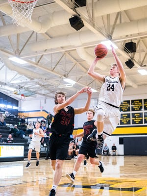 North Buncombe's Ren Dyer jumps up for a shot trailed by Rosman's Samuel Chappell during their game in Tuscola's Holiday Classic tournament Thursday, December 28, 2017.