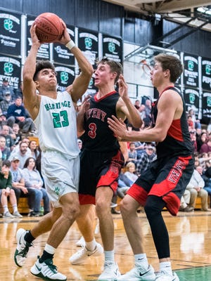 Mountain Heritage's Brandon Aumiller looks to the basket guarded by Avery's Ryder Seiz during their game Friday, January 19, 2018.