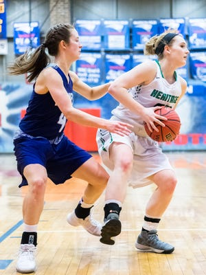 Mountain Heritage's Ciera Chandler maneuvers around Mitchell's Eden Phillips during their Western Highlands tournament game February 16, 2018.