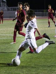 Erick Serrano shooting the ball into the goal. The Desert Mirage varsity soccer team won Tuesday's home playoff game against Oxnard (CA) by a score of 2-1.