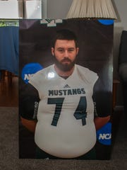 A poster-board of Michael Mazza in his Mount Ida football uniform, with the NCAA logo in the background, sits at the Mazza family home in Ocean Township.