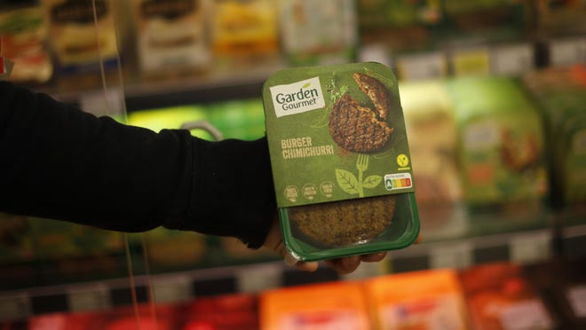 A store clerk shows a plant based burger at a supermarket chain in Brussels, Friday, Oct. 23, 2020. European lawmakers rejected Friday proposals that could have prevented plant-based products without meat from being labeled sausages or burgers. Following the votes on agricultural products at the European Parliament, the so-called veggie burgers, soy steaks and vegan sausages can continue to be sold as such in restaurants and shops across the union.