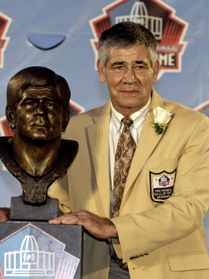 Chris Hanburger poses with a bust of himself during the induction ceremony at the Pro Football Hall of Fame Saturday, Aug. 6, 2011, in Canton, Ohio.