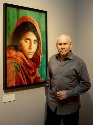 Photographer Steve McCurry poses in front of photographs of the 'Afghan Girl' featured in the exhibit 'Steve McCurry. Overwhelmed by life' at the Museum of Arts and Crafts in Hamburg, Germany, on June 27, 2013.