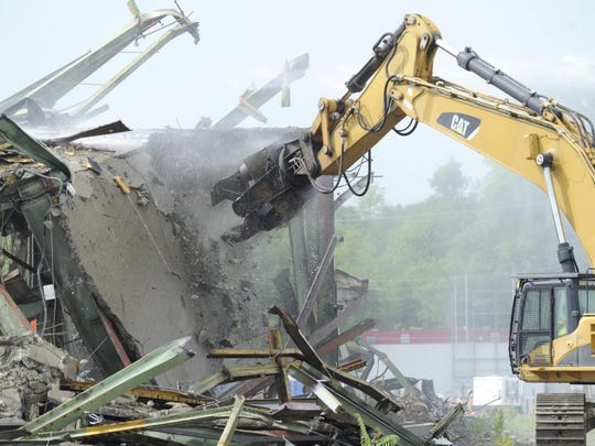 Cranes demolish the last standing structures of K-31 in Oak Ridge on Friday, June 26, 2015. Built in 1951 to enrich uranium for national defense, the facility is the fourth of five gaseous diffusion buildings to be demolished at East Tennessee Technology Park, which was part of the Manhattan Project. Neighboring K-27 will be the final building demolished. (ADAM LAU/NEWS SENTINEL)
