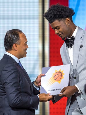 NBA deputy commissioner Mark Tatum hands Phoenix Suns player Josh Jackson the number one pick card during the 2018 NBA draft lottery.