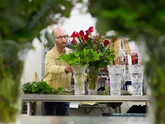 Floral designer Greg Wright, of Evansville, prepares