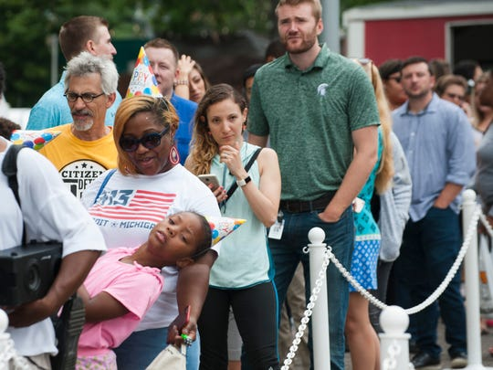 Alaura Brooks, 8, of Detroit leans out to see how long the ice cream line is, while waiting on free Hudsonville ice cream with her mother Alexis Brooks and a host of other people waiting on a scoop during Hudsonville's free ice cream party in Cadillac Square in downtown Detroit to celebrate the city's 317th birthday on Tuesday, July 24, 2018.