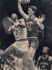 Chris Bowles, 53, defending against Wisconsin's Willes Simms, 23, while USI's Rick Stein watches the action in 1990.