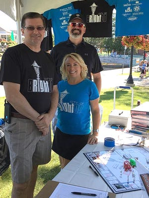 Brighton Mayor Pro Tem Shawn Pipoly, left, City Manager Nate Geinzer and Councilwoman Renee Pettengill show off the Brightonopoly game, along with 150th anniversary t-shirts, during the recent Taste of Brighton event.