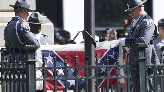 An honor guard from the South Carolina Highway patrol removes the Confederate battle flag from the Capitol grounds in Columbia, S.C., Friday, ending its 54-year presence there.