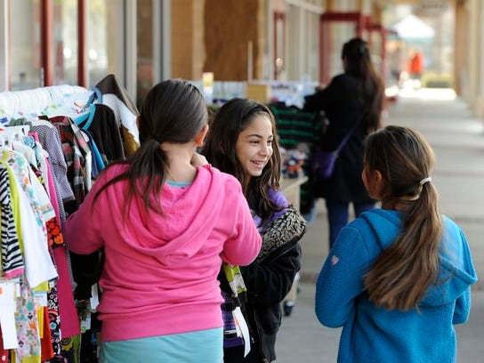Alondra Sanchez, left, Alex Pelayo and Izabel Pelayo browse sale items on the sidewalk in front of Carter's at Tulare Outlet Center after Christmas in 2011. Alex and Izabel are cousins.