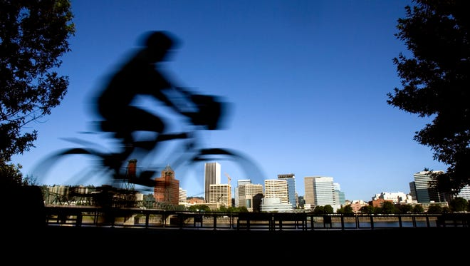 In this July 10, 2008, file photo, a bicyclist travels along the east bank of the Willamette River in Portland.