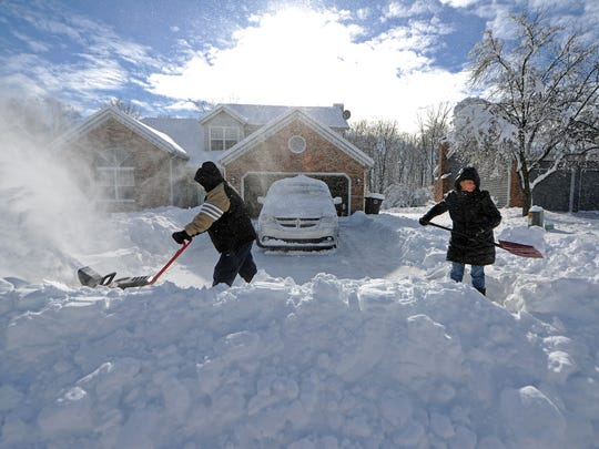 Ron and Janet Moore used a snowblower and a shovel Jan. 7 to clear the more than 3-foot-high mound left by a snowplow at the end of their driveway on Indianapolis' Northeastside. A storm two days earlier dumped 11.4 inches of snow on the city.