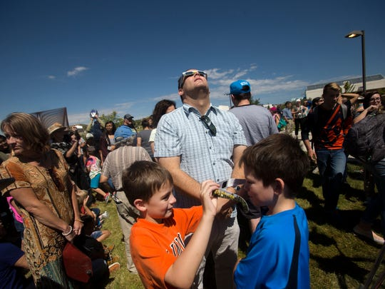 At center, Teun Fetz, the music professor at San Juan College, watches the eclipse, Monday during a viewing event at San Juan College in Farmington, N.M.