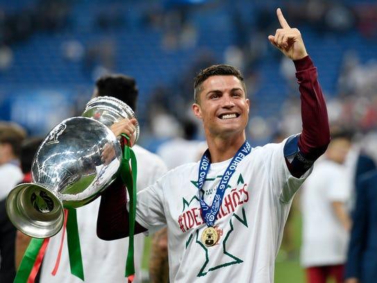Cristiano Ronaldo, sostiene el trofeo de Campeón.