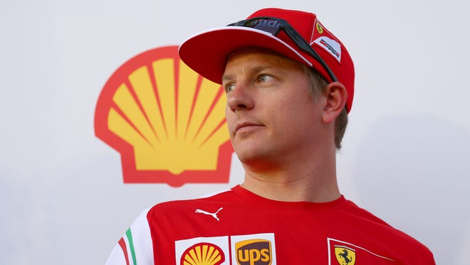 Kimi Raikkonen of Finland and Ferrari looks on as he speaks with members of the media after driving a Shell Eco-Marathon car at a Shell fuel station during previews ahead of the United States Formula One Grand Prix on October 30, 2014 in Austin, United States.