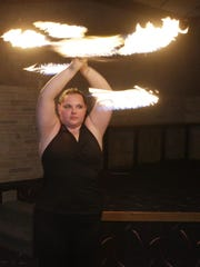 Valerie Ringwell of Sheboygan, works a fire baton during a demonstration of her fire eating skills, Thursday, April 12, 2018, in Sheboygan Falls, Wis. Ringwell is creating a calendar after being sexually assaulted with hopes to help others with assaults. She learned how to eat fire so she could conquer one of her fears.
