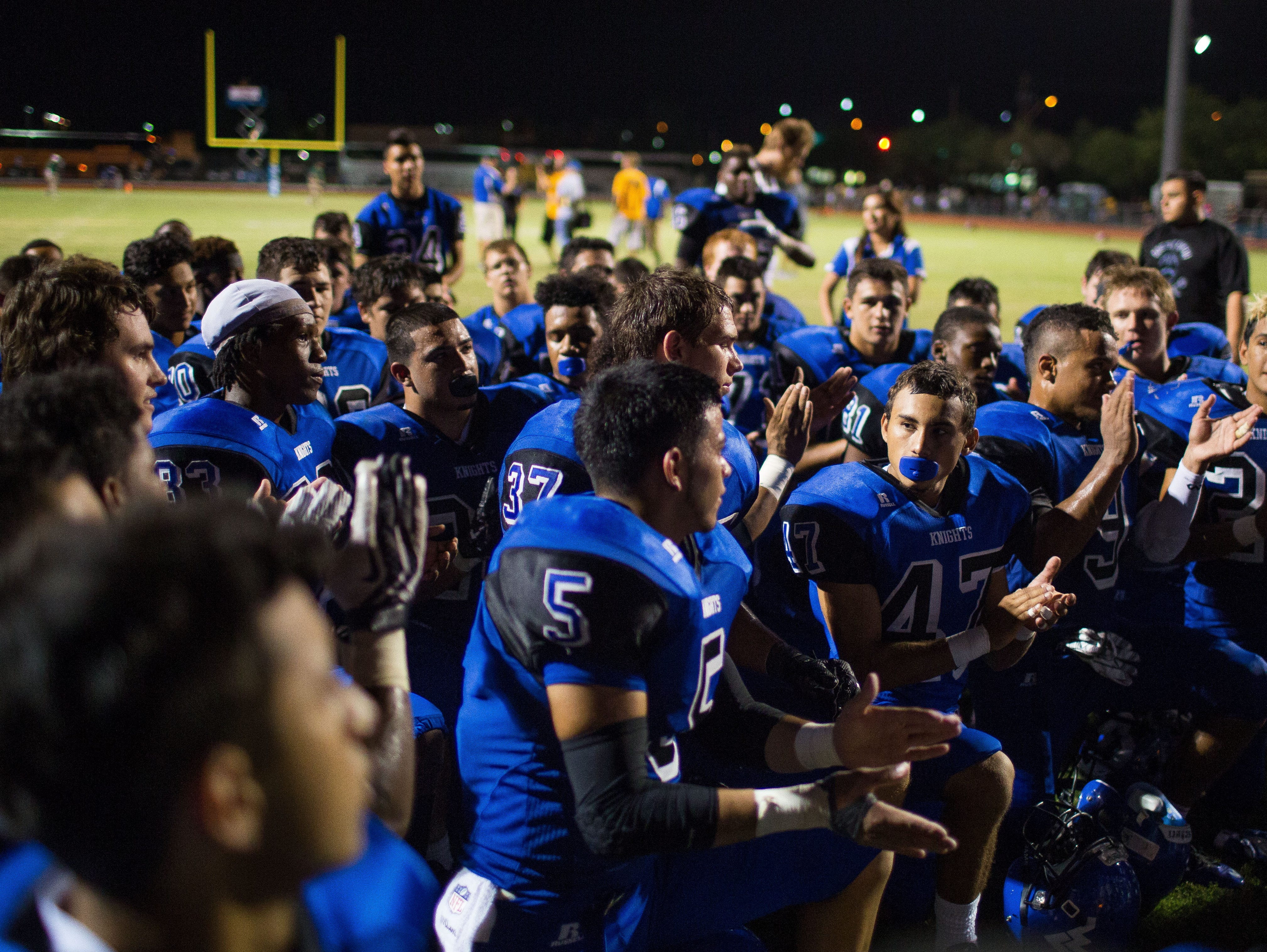 The Westview High School football team takes a knee to listen to coaches post game after their win over Basha High School at a Westview High School football game September 25, 2014 in Avondale.