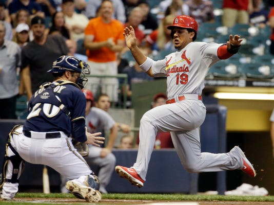 St. Louis Cardinals' Jon Jay scores past Milwaukee Brewers catcher Jonathan Lucroy during the first inning of a baseball game Thursday, Sept. 4, 2014, in Milwaukee. Jay scored from second on a hit by Yadier Molina. (AP Photo/Morry Gash)