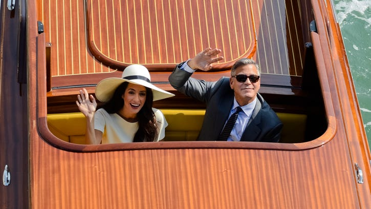 George Clooney and Amal Alamuddin on a boat after their Venice wedding late last month. His smile tells John Kiesewetter that he's still the same old George who grew up on his father's live TV variety shows here, attended schools in Northern Kentucky and sold women's shoes at McAlpin's in Crestview Hills before going to Hollywood in 1982.<252> <137>Actor George Clooney, right, andAmal Alamuddin wave from a boat as they leave after a civil weeding ceremony at the town hall in Venice, Italy, Monday, Sept. 29. , 2014. George Clooney married human rights lawyer Amal Alamuddin Saturday, the actor's representative said, out of sight of pursuing paparazzi and adoring crowds. (AP Photo/Luigi Costantini)<137>