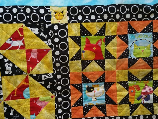 This quilt featuring dogs and cats is the type of hand-made