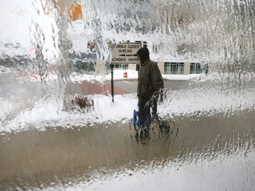 Pedestrians take their time walking in the icy conditions during the ice storm Monday afternoon downtown Indianapolis at the corner of East and Market Streets.