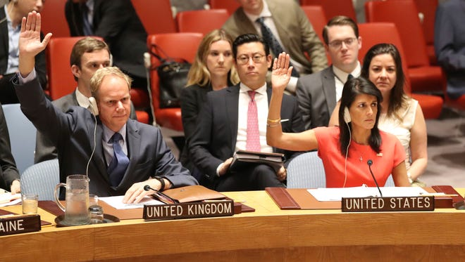 British Ambassador to the United Nations Matthew Rycroft, left, and American Ambassador to the United Nations Nikki Haley vote during a Security Council meeting on a new sanctions resolution that would increase economic pressure on North Korea to return to negotiations on its missile program,  Aug. 5, 2017.