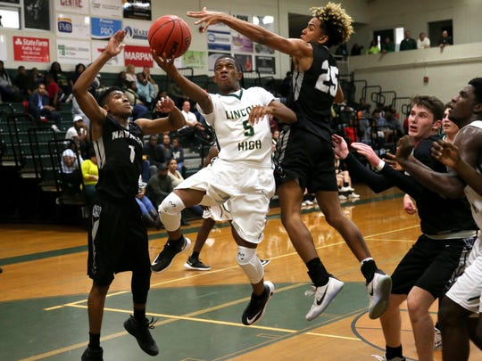 Lincoln's Tionne Rollins, seen here against Navarre, made the game-winning basket in overtime in a 62-61 overtime win at Creekside. Rollins scored 10 points and the Trojans made the 8A state tournament.