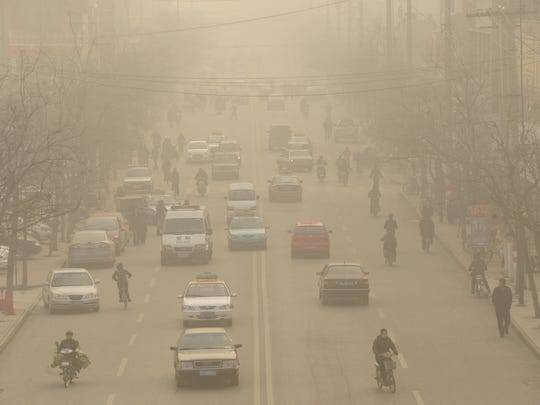 "(FILES) - A file photo taken on December 9, 2009 shows smog down a main street of Linfen, in China's Shanxi province, regarded as one of the cities with the worst air pollution in the world. The United States and China announced on November 12, 2014 at a Beijing summit an action plan on greenhouse emissions as part of a ""historic"" pact that was acclaimed by climate scientists but denounced by US Republicans as a job-killer. The United States set a goal to cut its own emissions of the gases blamed for climate change by 26-28 percent from 2005 levels by 2025. The declaration came as Obama met his Chinese counterpart Xi Jinping for talks in Beijing. AFP PHOTO / Peter PARKSPETER PARKS/AFP/Getty Images"