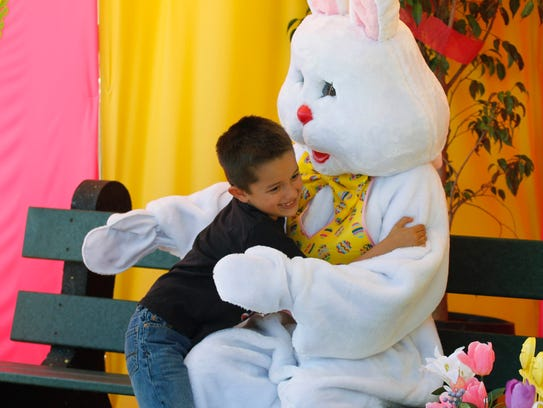 Sean Tapia, 6, gives a hug to the Easter Bunny after