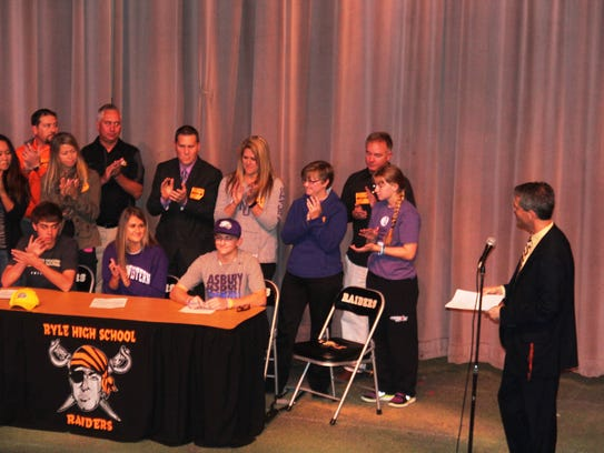 Principal Matt Turner addresses a group of Ryle High School students as they sign letters of intent for college.